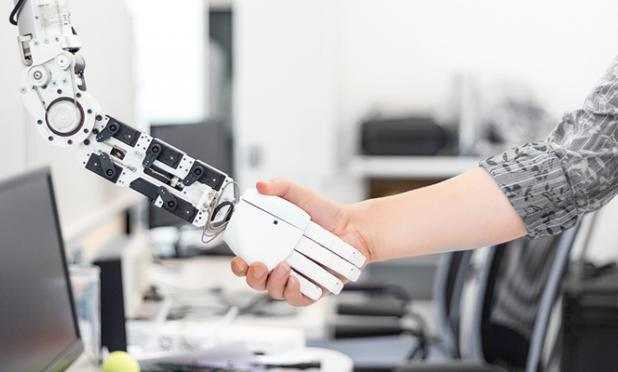 Human shaking hands with a robot arm.