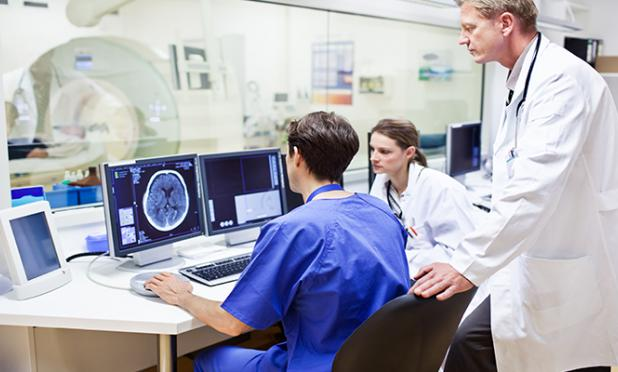 Doctor talking to radiologists at a computer with an MRI machine in the background.